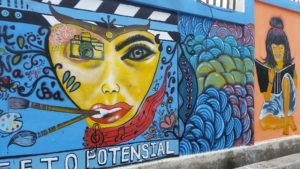 Women Potential -A mural by young women who see their potential and who have goals - Located on the wall of the football stadium in Dili, Timor Leste depicting a face with various art profession equipment and a young woman reading a book - taken 29 feb 2020